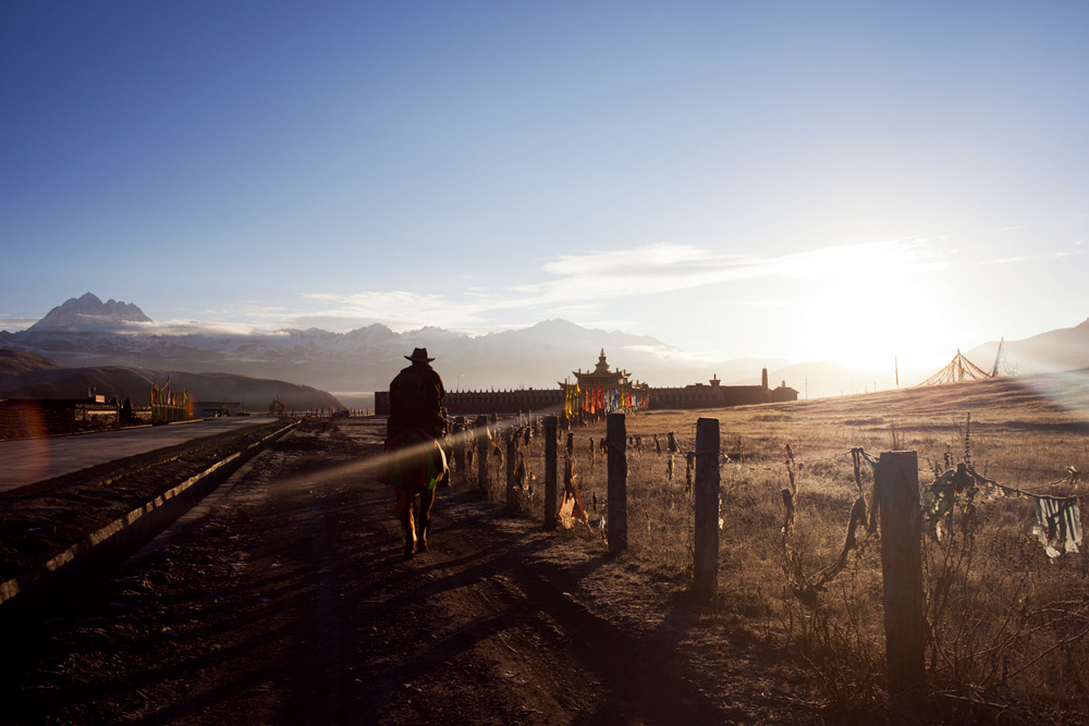 Tibetan horseman riding out into the sunrise outside Tagong Village with Mt. Yala on the horizon. Garzê Tibetan Autonomous Prefecture of western Sichuan Province, China.